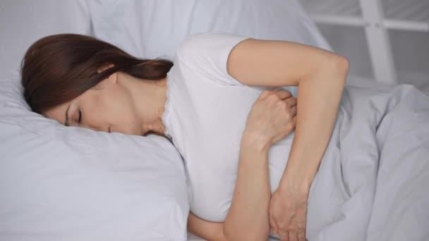žena ležící v posteli a trpící bolestí žaludku