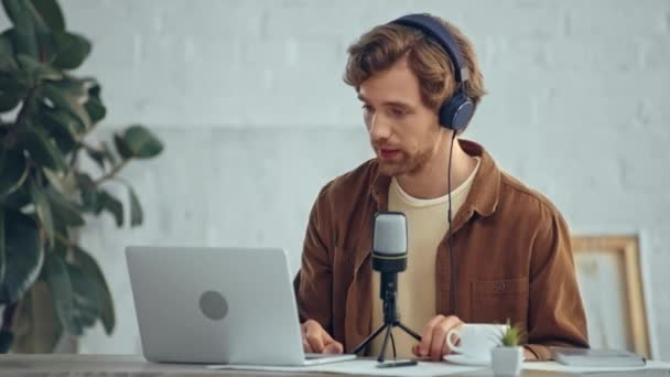 Photo man in headphones with mic broadcasting while using laptop