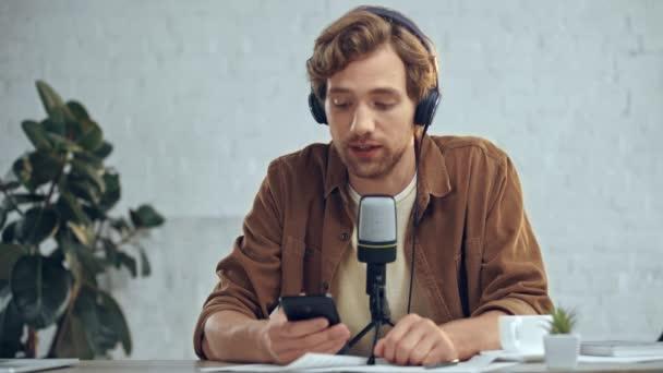 férfi fejhallgató-val MIC műsorszórás és használ smartphone