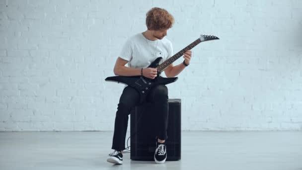 mladý hudebník hrající elektrickou kytaru na reproduktoru