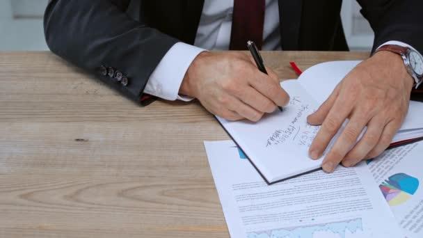 Ausgeschnittene Ansicht des Geschäftsmannes, der in Notizbuch schreibt und Vertrag unterschreibt