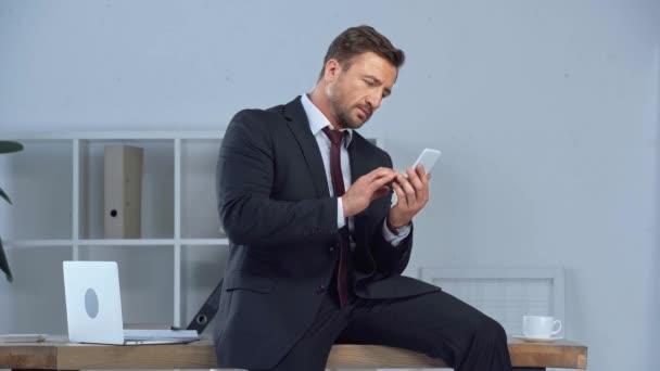 dospělý obchodník sedí na psacím stole a používá smartphone