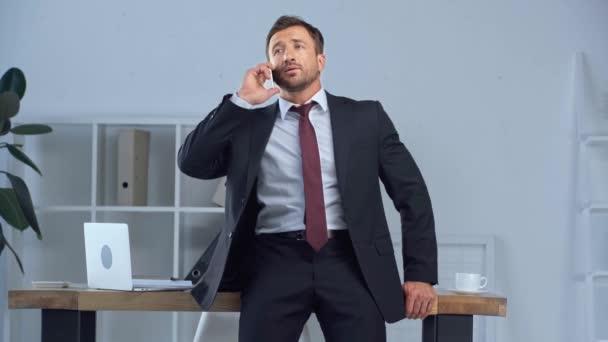 dospělý obchodník sedí na stole a mluví na telefonu Smartphone