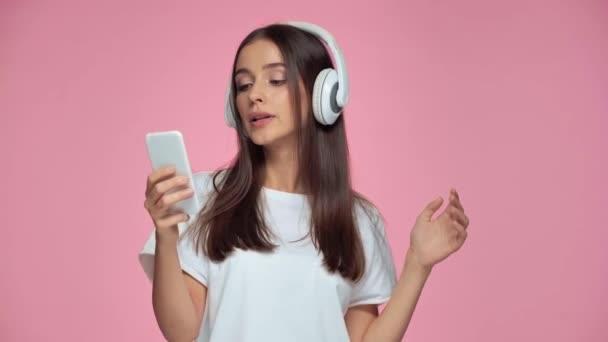 Mädchen mit Kopfhörern tanzen und singen isoliert auf rosa