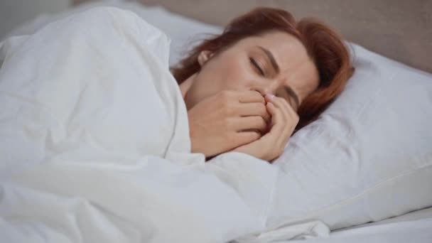 sick woman coughing while lying in bed under blanket