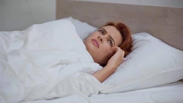 Unzufriedene Frau im Bett verstopft Ohren und leidet unter Lärm