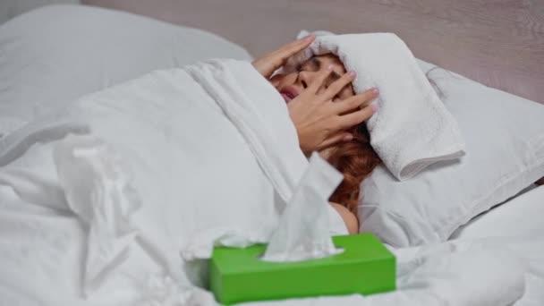 Kranke Frau hustet, während sie unter Decke mit Handtuch auf dem Kopf liegt