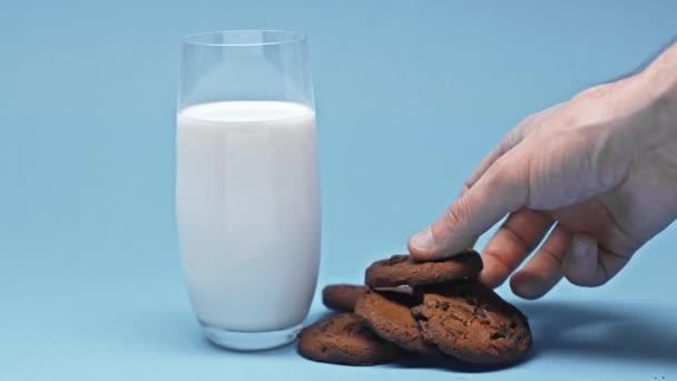 Oříznutý pohled muže máčení cookie ve sklenici mléka na modrém pozadí
