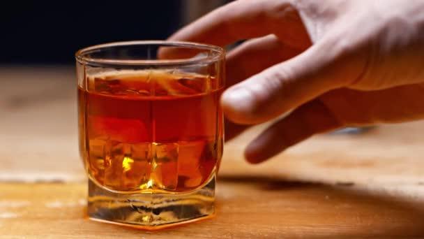 částečný pohled om taking glass of whiskey isolated on black, slow motion