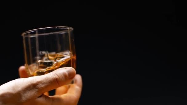 mužská ruka se sklenicí whisky a kostkami ledu izolovaná na černém, zpomaleném filmu