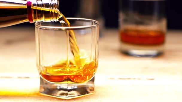 zpomalený pohyb whisky z láhve do skla izolovaného na černém