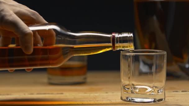oříznutý pohled na muže, jak nalévá whisky do skla izolovaného na černém