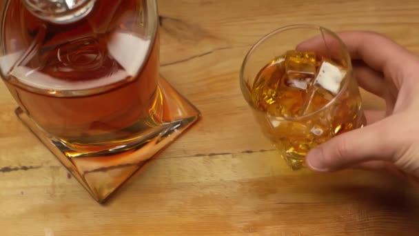 oříznutý pohled na muže držícího sklenici whisky poblíž karafy na dřevěném stole