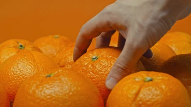 Cropped view of man taking and putting orange isolated on orange