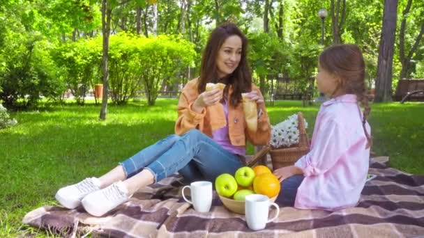 mother and daughter eating baguette on picnic