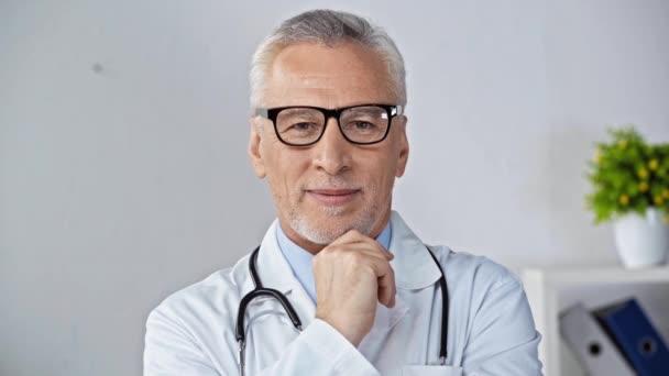 Reifer Arzt mit Brille, lächelndem Kinn und winkender Hand
