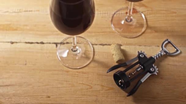 korková, vývrtka a vinné sklenice s červeným vínem na dřevěném podkladu