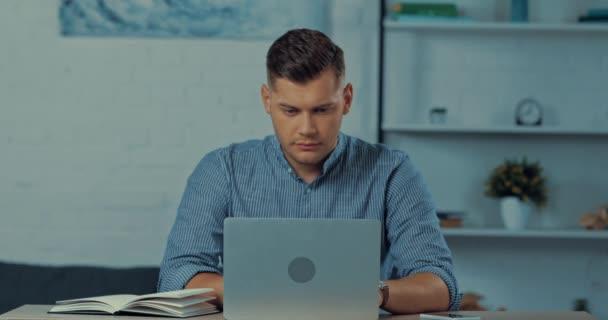 jóképű szabadúszó használ laptop és írás notebook