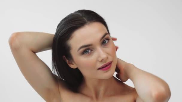 Krásná nahá žena dotýkající se vlasů a usmívající se izolované na šedé