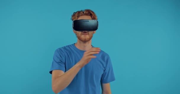 bärtiger Rotschopf gestikuliert in vr Headset isoliert auf blau