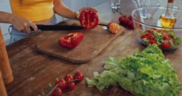 abgeschnittene Ansicht einer Frau, die rote Paprika in der Nähe einer Schüssel mit Salat schneidet
