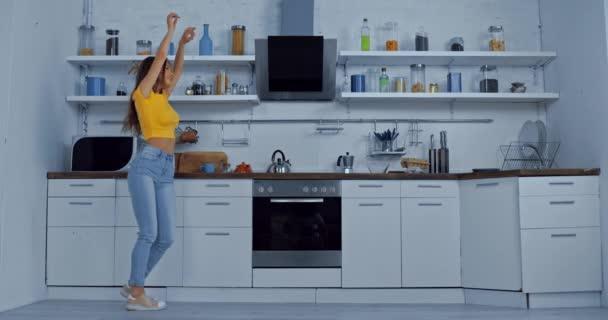 veselá žena tančící v moderní kuchyni