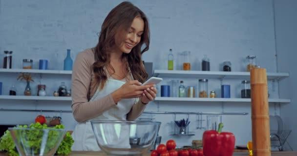 glückliche Frau in Schürze mit Smartphone nahe Zutaten auf dem Tisch