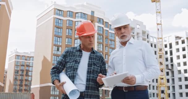 Engineer and builder with gadget and blueprint talking on construction site