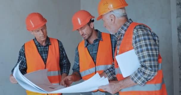 Stavbaři s digitálním tabletem sledující plány na staveništi