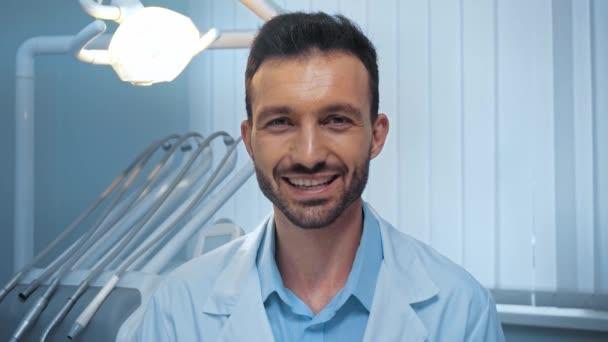 Lächelnder Zahnarzt zeigt in Klinik Geste vor Kamera