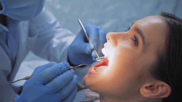 Doktor používající zubní nástroje při práci s pacientem na zubní klinice