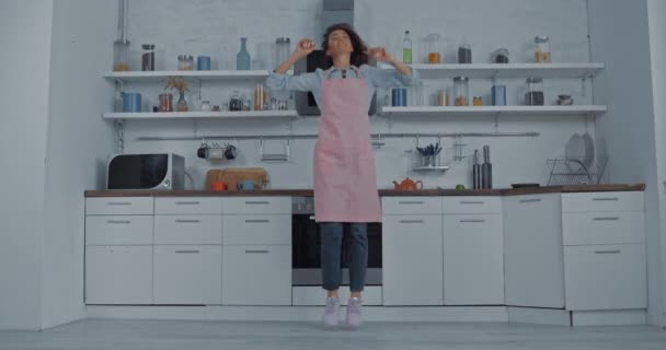 Young woman in apron dancing in kitchen