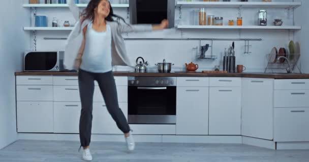 Těhotná žena tanec a skákání v kuchyni