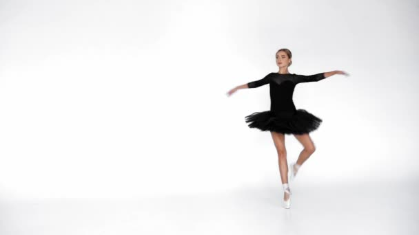 Junge Ballerina im schwarzen Ballettrock, der sich dreht und auf weißem Hintergrund tanzt