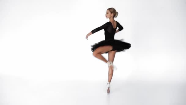 Graceful ballerina performing classical dancing moves on white background
