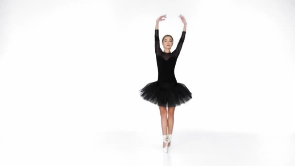 Young ballerina in black ballet skirt dancing on pointe on white background