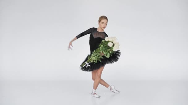 Young ballerina with roses performing classical ballet moves on white background