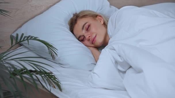 fiatal szőke nő mosolyog, miközben alszik otthon