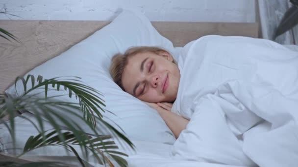 selektivní zaměření ženy protahování při probuzení v ložnici