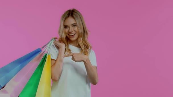 Blondýny žena s nákupními taškami gestikulující izolované na fialové