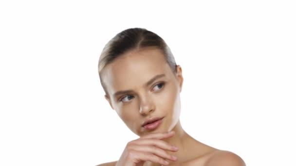Portrét mladé ženy dotýkající se obličeje s rukama izolovanými na bílém