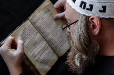 A Hasidic Jew reads Siddur. Religious orthodox Jew with a red beard and with pace in a white bale praying. On the bale is an inscription Rabbi Nahman from Uman. Closeup