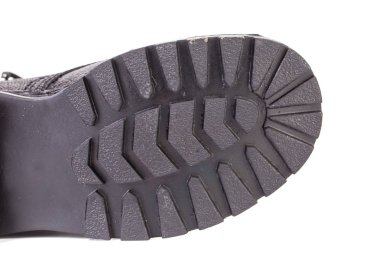 Close-up of corrugated sole of worker boots. It is located in a white background.