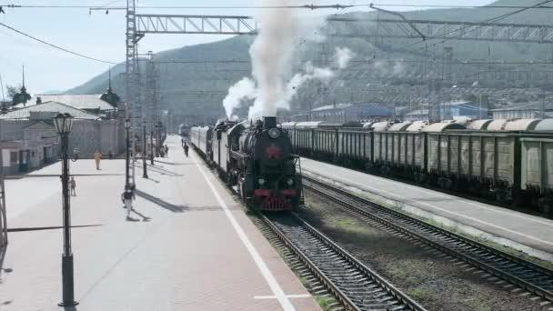 Slyudyanka, region Irkutsk, Rusko - 18. srpna 2018: staré turistické lokomotiva náklady na nádraží. Z potrubí je cigáro a zpod kola párů. Turisté jdou podle peron a jsou fotografoval.