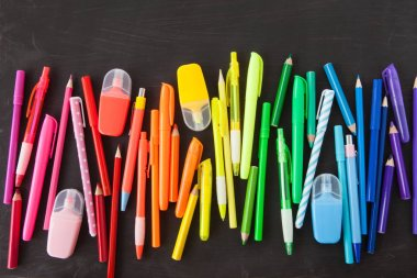 Variety of colorful pens in a rainbow on black background