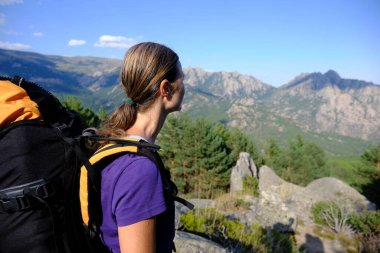 Rear view of woman with backpack looking at mountain