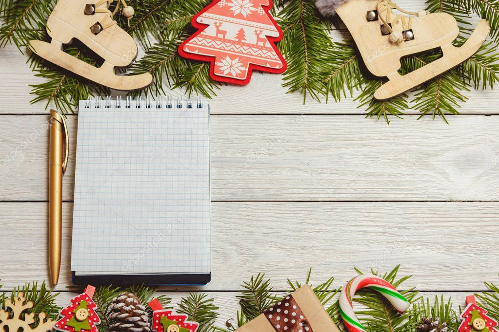 White wooden christmas background with fir branches, cones, decor, notebook, top view, copyspace.
