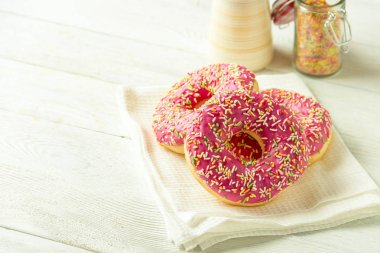 Donut on a kitchen towel and on a wooden table. Photo of sweets with copyspace.