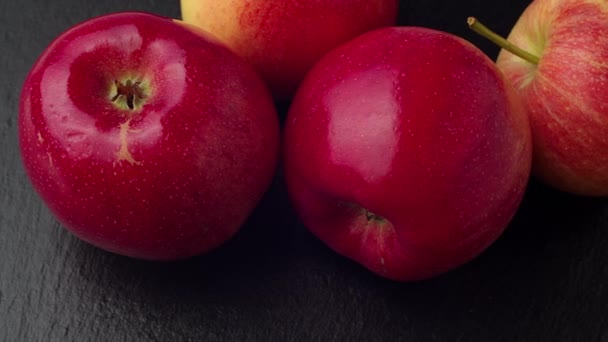 Delicious red apples pile on black stone board moving shot. 4K ProRes 422