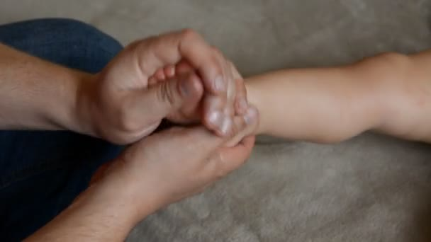 The male massage therapist does for the one year old baby boy child healing  rehabilitation recovery massage after suffering a cerebral circulation  disorder, a brain stroke, a right-sided hemiparesis